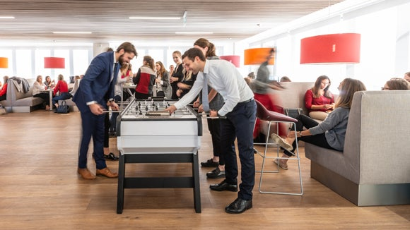 Colleagues playing foosball in the office