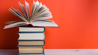 Pile of books against orange background