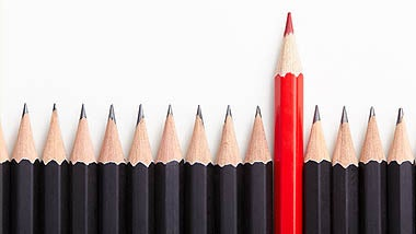 Row of black pencils with one red pencil standing out