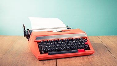 Red and black typewriter against green background