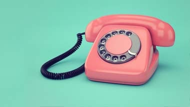 Pink telephone against green background