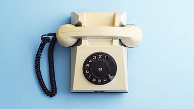 Old receiver telephone against blue background